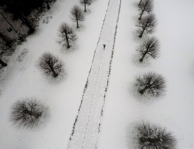 A person walks through the grounds of the Parish Church of Saint Mary and All Saints, in Whitmore, Staffordshire, Britain, December 28, 2020. (Photo by Carl Recine/Reuters)