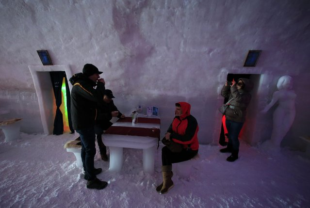 Tourists drink warm beverages and take pictures inside the Balea Lac Hotel of Ice in the Fagaras mountains January 29, 2015. (Photo by Radu Sigheti/Reuters)