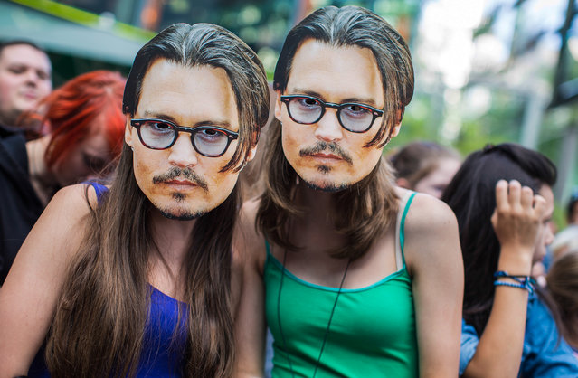 "Two girls wear masks showing U.S. actor Johnny Depp as they wait for the German premiere of the movie ""The Lone Ranger"" in Berlin, Germany, Friday, July 19, 2013. (Photo by Gero Breloer/AP Photo)"