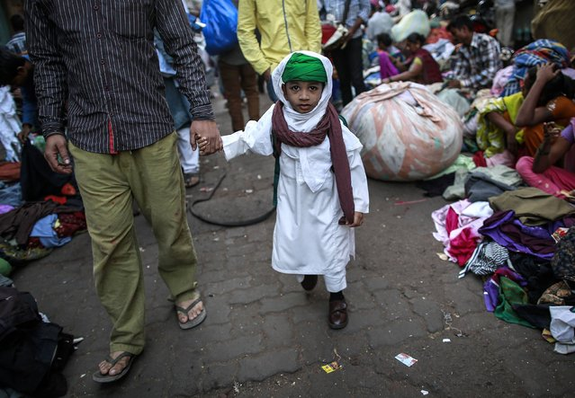 A boy walks with his father to school through a second-hand street side clothing market in Mumbai January 28, 2015. (Photo by Danish Siddiqui/Reuters)