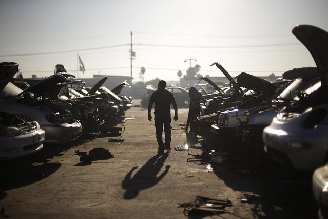 In this Wednesday, November 11, 2015 photo, a man walks between junk cars at Aadlen Brothers Auto Wrecking, also known as U Pick Parts, in the Sun Valley section of Los Angeles. (Photo by Jae C. Hong/AP Photo)