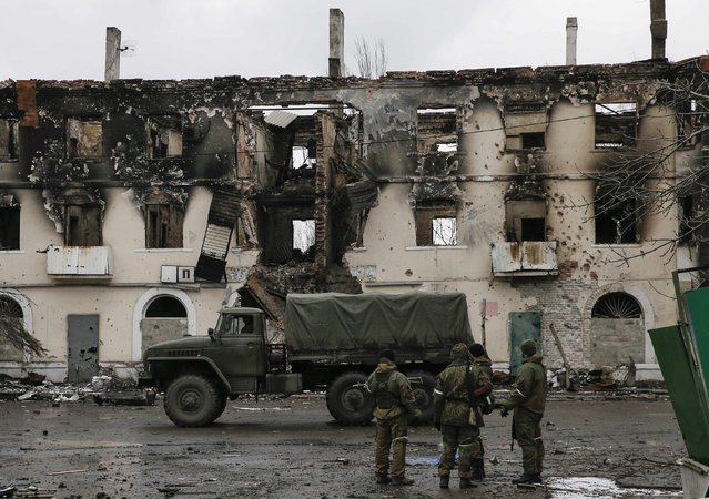 Members of the armed forces of the separatist self-proclaimed Donetsk People's Republic gather near a building destroyed during battles with the Ukrainian armed forces in Vuhlehirsk, Donetsk region, February 4, 2015. (Photo by Maxim Shemetov/Reuters)