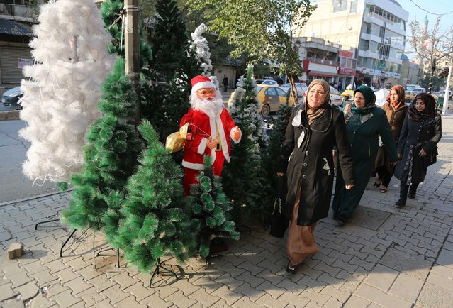 Iraqis pass by a shop selling Christmas decorations in the Karrada neighborhood of Baghdad, Iraq, Thursday, December 24, 2015. Christians around the world will celebrate Christmas on Friday. (Photo by Karim Kadim/AP Photo)