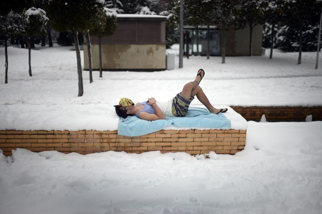 A boy lies down on a beach towel at the Florida park in the Spanish Basque town of Vitoria following heavy snow, February 6, 2015. (Photo by Vincent West/Reuters)