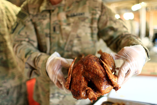 A U.S. soldier serves turkey to fellow soldiers to celebrate Thanksgiving Day inside the U.S. army base in Qayyara, south of Mosul, Iraq November 24, 2016. (Photo by Thaier Al-Sudani/Reuters)
