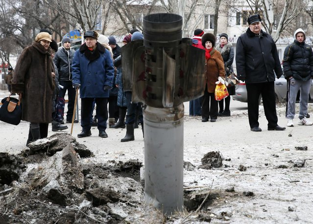 People look at the remains of a rocket shell on a street in the town of Kramatorsk, eastern Ukraine February 10, 2015. (Photo by Gleb Garanich/Reuters)