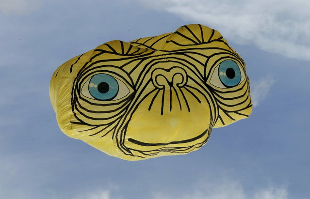 A balloon depicting the face of alien movie character E.T. is seen in the sky at the 15th Solar Balloon Festival in Envigado, Colombia December 31, 2015. (Photo by Fredy Builes/Reuters)