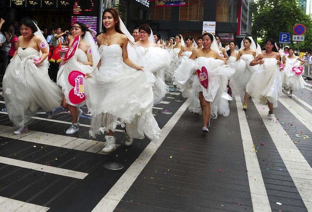 Women in wedding gowns participate in a brides' race organized by a shopping mall to celebrate the upcoming Qixi Festival in Guangzhou, China, on August 12, 2013. The Qixi Festival, also known as the Double Seven Festival, which falls on the seventh day of the seventh month in the Chinese lunar calendar, is the Chinese version of Valentine's Day. The festival falls on August 13 this year. (Photo by Reuters)