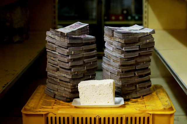 A kilogram of cheese is pictured next to 7,500,000 bolivars, its price and the equivalent of 1.14 USD, at a mini-market in Caracas, Venezuela August 16, 2018. It was the going price at an informal market in the low-income neighborhood of Catia. (Photo by Carlos Garcia Rawlins/Reuters)