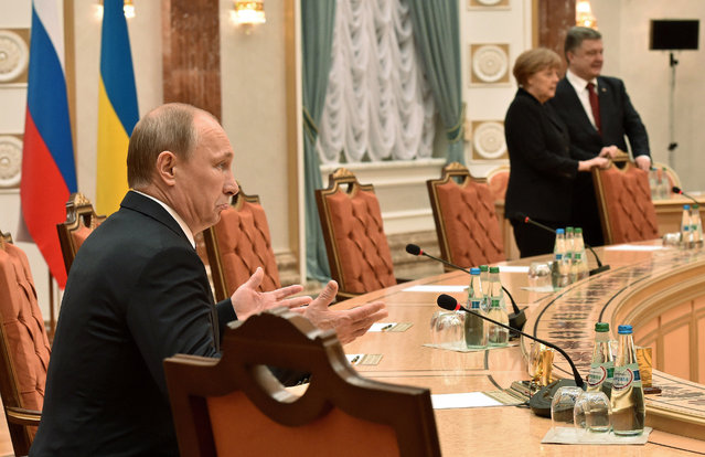 Russian President, Vladimir Putin, left, gestures as German Chancellor, Angela Merkel and Ukrainian President, Petro Poroshenko, stand nearby during a meeting in Minsk, Belarus, Wednesday, February 11, 2015. Leaders of Russia, Ukraine, France and Germany are gathering for crucial talks in the hope of negotiating an end fighting between Russia-backed separatist and government forces in eastern Ukraine. (Photo by Kirill Kudryavtsev/AP Photo)