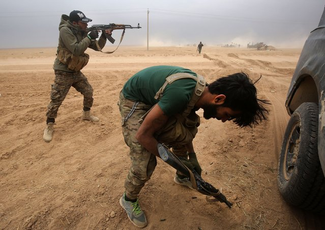Iraqi Shiite fighters from the Hashed al- Shaabi (Popular Mobilisation) paramilitaries clash near the village of Tal Abtah, south of Tal Afar, on November 30, 2016, during a broad offencive by Iraq forces to retake the city Mosul from jihadists of the Islamic State group. (Photo by Ahmad Al- Rubaye/AFP Photo)