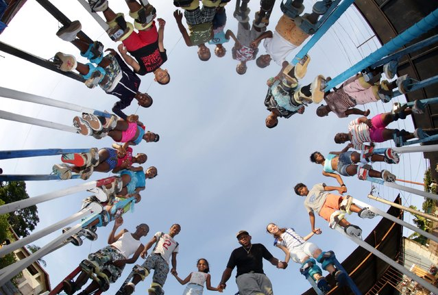 The members of the Keylemanjahro School of Art and Culture gather in a circle for a group photo at their base yard in Harding Place, Cocorite, just West of the capital Port-of-Spain, Trinidad, on February 8, 2015. (Photo by Andrea De Silva/Reuters)