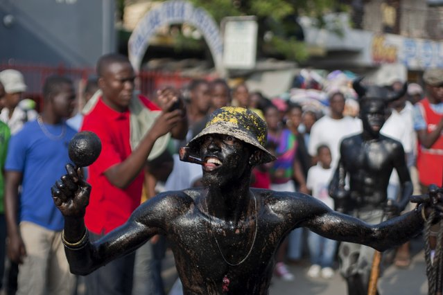 A man, his body smothered in clay mud and oil, performs in a street parade, kicking off Carnival celebrations in Port-au-Prince, Haiti, Sunday, February 15, 2015. (Photo by Dieu Nalio Chery/AP Photo)