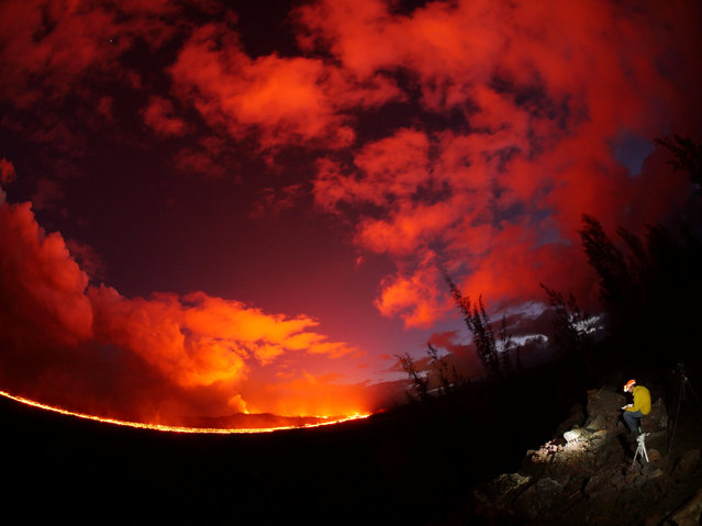 A USGS geologist making observations of the fissure 8 lava channel at sunset is pictured in this July 3, 2018 fisheye lens handout photograph near the Kilauea volcano eruption in Hawaii, U.S. (Photo by USGS/Handout via Reuters)