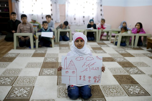 "Syrian refugee Islem Halife, 11, shows a drawing of her home in Syria, as she sits in a classroom where she learns the Quran in Nizip refugee camp in Gaziantep province, Turkey, December 13, 2015. The writing in Arabic in the drawing reads, ""God is great"". Syria's conflict has left hundreds of thousands dead, pushed millions more into exile, and had a profound effect on children who lost their homes or got caught up in the bloodletting. (Photo by Umit Bektas/Reuters)"