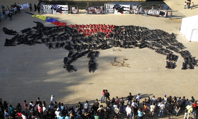 Members of the non-profit animal rights organization AnimaNaturalis lie down to form the shape of a bull, during a protest against bullfighting in the Park of Wishes in Medellin February 21, 2015. (Photo by Fredy Builes/Reuters)