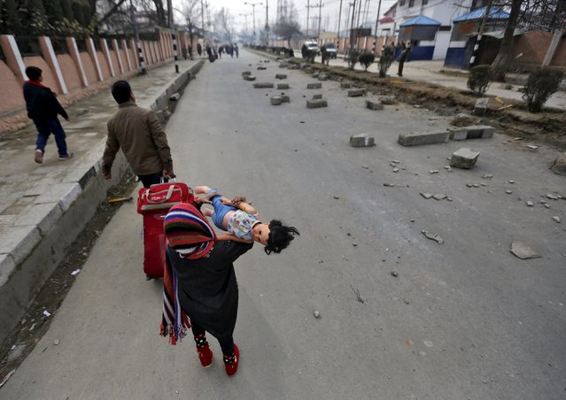 A young tourist carries a doll as she walks on a road during a protest in Srinagar, January 14, 2016. (Photo by Danish Ismail/Reuters)