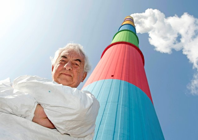 "French conceptual artist Daniel Buren poses in front of his work, the Chemnitz chimney 2013, in the power plant ""eins energie"" in Chemnitz, eastern Germany, Tuesday, October 8, 2013. The artist has chosen seven colors representing the new identity of the tower : traffic yellow, signal violet, melon yellow, sky blue, yellow green, strawberry red, and aquamarine. From the top of its 302 meters, the 302-meters (991 ft)  Chemnitz chimney is the highest structure in the German state of Saxony. (Photo by Jens Meyer/AP Photo)"