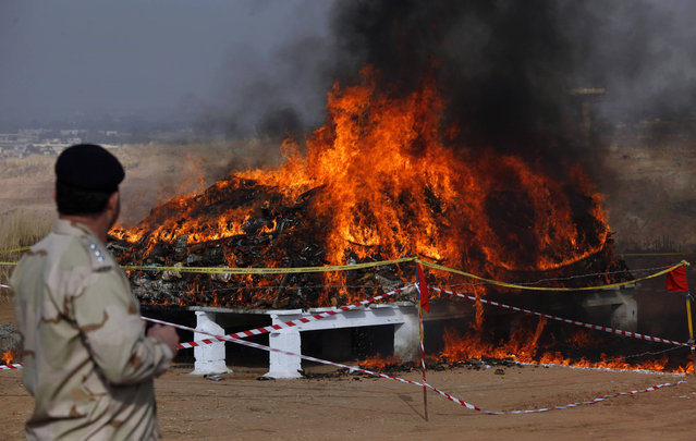 An officer from the anti narcotics force looks at a burning pile of seized narcotics at a ceremony on the outskirts of Islamabad, Pakistan, Thursday, December 15, 2016. Authorities torched some 52 metric tones of narcotics and bottles of alcohol seized in various raids. Head of ANF, Maj. Gen. Nasir Dilawar Shah said worth $152 million drugs were burned as a part of Pakistan's campaign aimed at eradicating the menace of drugs from the society. (Photo by Anjum Naveed/AP Photo)
