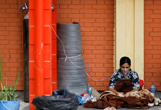 A patient receives oxygen as she waits outside the passage of a hospital due to a lack of free beds inside the hospital for coronavirus disease (COVID-19) patients, as the second major coronavirus wave surges in Kathmandu, Nepal, May 10, 2021. (Photo by Navesh Chitrakar/Reuters)