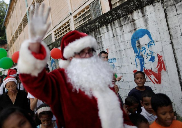 Santa Claus walks past a mural depicting Venezuela's late President Hugo Chavez during a visit to residents of the slum of Petare in Caracas, Venezuela, December 11, 2016. (Photo by Ueslei Marcelino/Reuters)