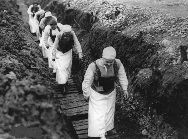American nurses carrying gas masks walk through a trench in France, 1918. (Photo by Hulton Archive/Getty Images)