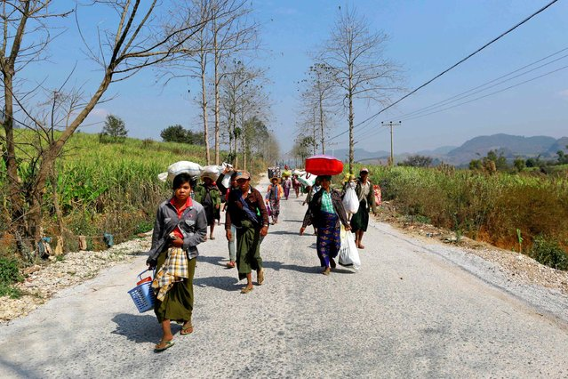 Refugees who have been displaced by recent violence, walk down a road with bundles of belongings, in Laukkai February 17, 2015. (Photo by Soe Zeya Tun/Reuters)