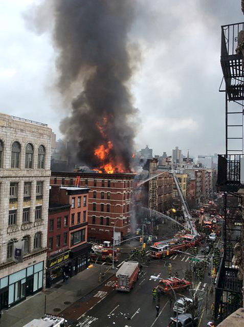 Fire shoots from the roof of a building after it collapsed and burst into flames in New York City's East Village as seen in this picture taken by Scott Westerfeld March 26, 2015.  Rescuers from the Fire Department of New York (FDNY) were headed to the location, which was on Second Avenue and East 7th Street in Manhattan, an FDNY spokeswoman said. (Photo by Scott Westerfeld/Reuters)