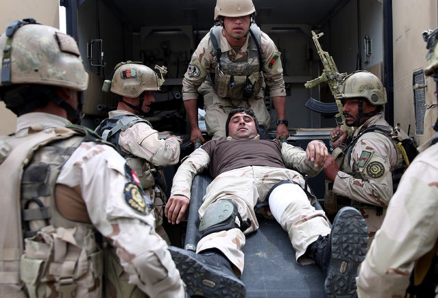 Afghanistan's interior ministry special forces carry their wounded colleague into an ambulance during a military exercise in Kabul, Afghanistan, Thursday, April 2, 2015. (Photo by Massoud Hossaini/AP Photo)