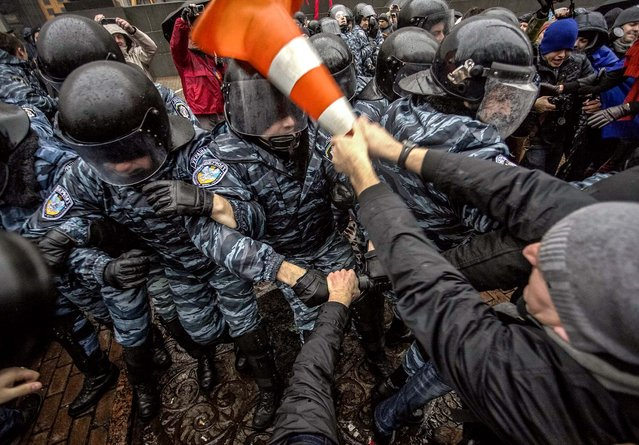 Good guy protester helps SWAT to install VLC media player (I'm kidding). A protester clashes with riot police during a rally supporting EU integration in front of the Ukrainian cabinet of ministers building in Kiev, on November 25, 2013. The European Union expressed strong disapproval on Monday of Russian pressure on Ukraine to reject an EU trade deal. (Photo by Dmytro Larin/Reuters)