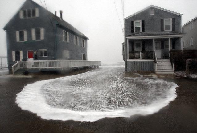 Seawater pushed by high winds flows between two homes in the Sand Hills neighborhood in Scituate, Mass., Monday, February 8, 2016. (Photo by Greg Derr/The Quincy Patriot Ledger via AP Photo)