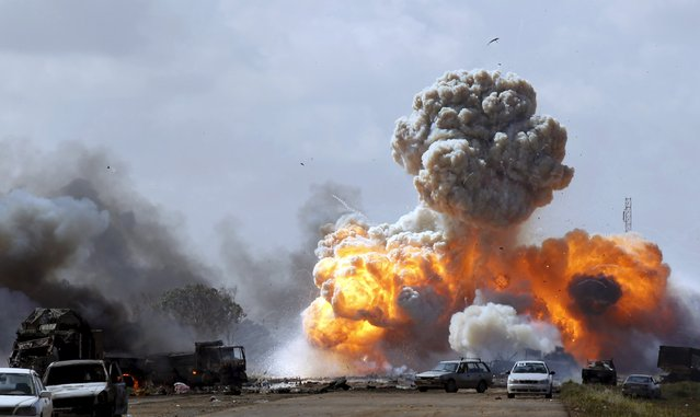 Vehicles belonging to forces loyal to Libyan leader Muammar Gaddafi explode after an air strike by coalition forces, along a road between Benghazi and Ajdabiyah March 20, 2011. The fifth anniversary of the Libyan uprising which overthrew dictator Colonel Muammar Gaddafi takes place on February 15. (Photo by Goran Tomasevic/Reuters)