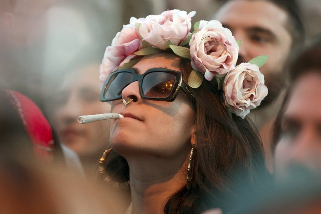 A woman smokes at the Coachella Valley Music and Arts Festival in Indio, California April 10, 2015. (Photo by Lucy Nicholson/Reuters)