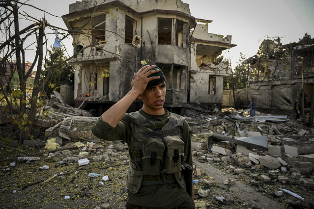An Afghan security personnel gestures as he stands guard at the site a day after a car bomb explosion in Kabul on August 4, 2021. (Photo by Wakil Kohsar/AFP Photo)