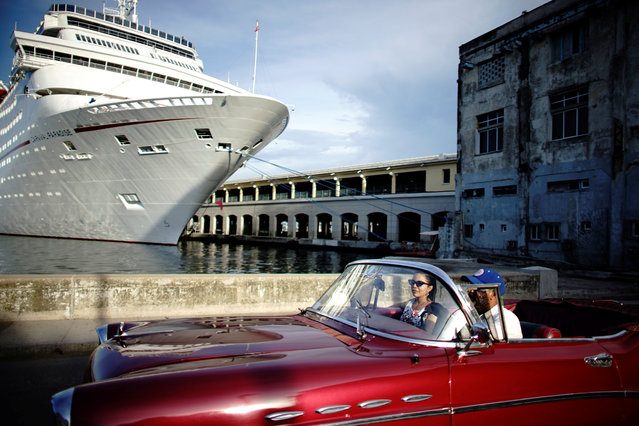People ride in a vintage car next to a cruise ship docked in Havana, Cuba on August 23, 2018. (Photo by Alexandre Meneghini/Reuters)