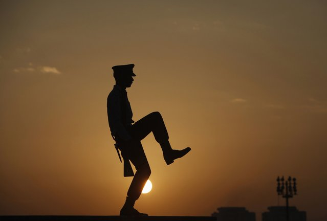 A cadet from Pakistan Air Force (PAF) is silhouetted against the morning sun during the guard mounting ceremony at the mausoleum of Mohammad Ali Jinnah in Karachi December 25, 2013. A contingent of Pakistan Military Academy (PMA) cadets mounted the guard at the mausoleum of Mohammad Ali Jinnah to mark his 137th birth anniversary. Jinnah is generally regarded as the founder of Pakistan. (Photo by Akhtar Soomro/Reuters)