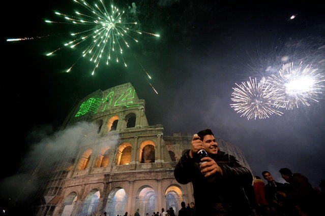 People celebrate the new year by the ancient Coliseum in Rome on January 1, 2014. (Photo by Filippo Monteforte/AFP Photo)