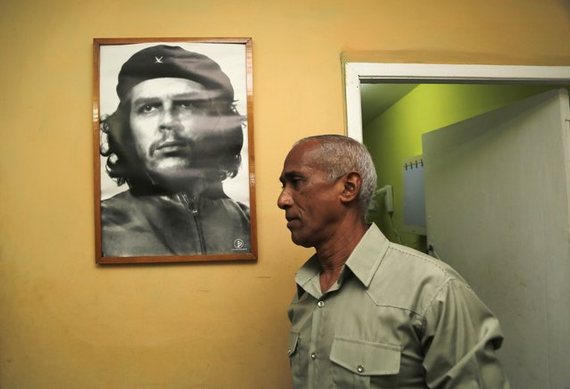 Dissident and candidate Hildebrando Chaviano walks beside a portrait of revolutionary leader Che Guevara before casting his ballot during Cuba's municipal elections at a polling station in Havana, Cuba, Sunday, April 19, 2015. (Photo by Desmond Boylan/AP Photo)