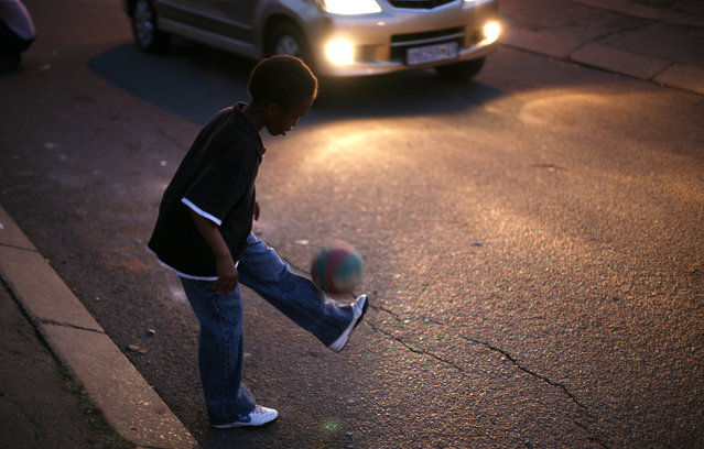A child plays with a soccer ball on a street in Soweto, South Africa's oldest township, November 23, 2008. (Photo by Radu Sigheti/Reuters)