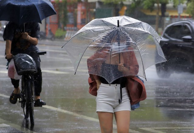 A woman struggles with her umbrella against powerful gusts of wind generated by Typhoon Chanthu in Taipei, Taiwan, Sunday, September 12, 2021. (Photo by Chiang Ying-ying/AP Photo)