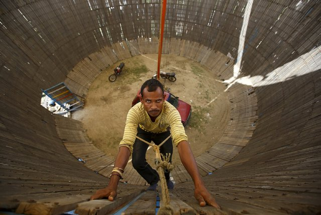 "A man climbs into the ""Well of Death"" attraction to fix the bolts during a fair in Bhaktapur April 20, 2015. (Photo by Navesh Chitrakar/Reuters)"