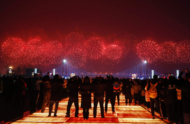 This photo taken on February 19, 2019 shows people watching a fireworks display during the Lantern Festival, which marks the end of Lunar New Year celebrations, in Dalian in China's northeastern Liaoning province. (Photo by AFP Photo/Stringer)