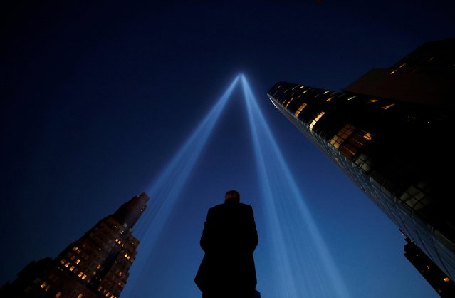 A person takes pictures of the Tribute in Light art installation on the day marking the 20th anniversary of the September 11, 2001 attacks in New York City, New York, U.S., September 11, 2021. (Photo by Carlos Barria/Reuters)