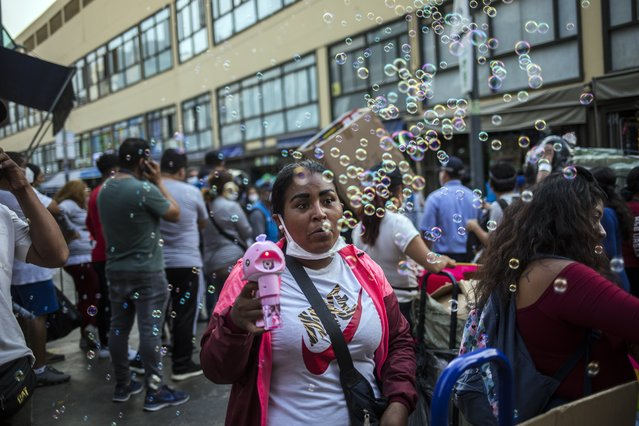 A street vendor sells a device that makes bubbles at the Mesa Redonda Market, a popular spot for Christmas shopping, amid the COVID-19 pandemic in Lima, Peru, Monday, December 21, 2020. (Photo by Rodrigo Abd/AP Photo)