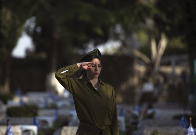 An Israeli soldier salutes as she stands next to graves of fallen soldiers during a ceremony at the Mount Herzl military cemetery in Jerusalem, ahead of Memorial Day April 19, 2015. (Photo by Ronen Zvulun/Reuters)