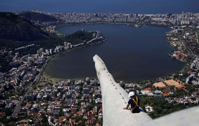 A worker inspects the arm of the Christ Redeemer statue. (Photo by Felipe Dana/Associated Press)