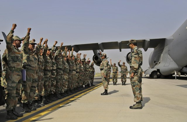 Indian soldiers on rescue mission to Nepal shout patriotic slogans before boarding an Indian Air Force aircraft near New Delhi, India, Sunday, April 26, 2015. (Photo by Altaf Qadri/AP Photo)