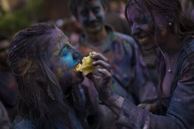 A reveler shares an apple with her friend during a Holi Festival in Madrid, Spain, Sunday, April 26, 2015. (Photo by Andres Kudacki/AP Photo)