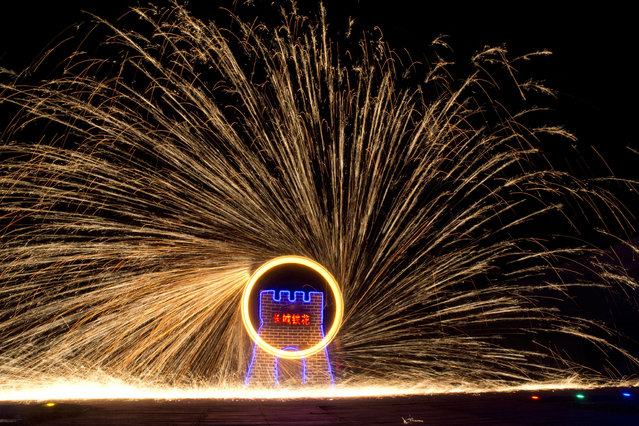 """Performers turn a wheel spinning molten iron to create sparks at the Great Wall Iron Sparks show in Yanqing county on the outskirts of Beijing, China, Saturday, January 28, 2017. An ancient craft that can be traced back several hundred years, the company is trying to revive the practice of throwing the molten iron and using the Lunar New Year period to showcase their latest choreography. Chinese character in center reads """"Great Wall Iron Sparks"""". (Photo by Ng Han Guan/AP Photo)"""