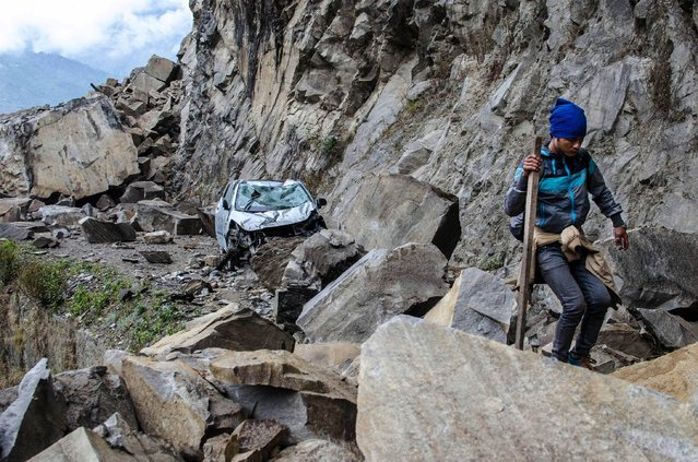 In this Monday, April 27, 2015 photo, a Nepalese man walks over fallen rocks and past a crushed car on the way to Dhunche, Nepal, a village in Langtang National Park, two days after a 7.8-magnatude earthquake hit the region. (Photo by Joe Sieder via AP Photo)